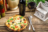 Freshly pizza served with red wine — Stock Photo