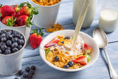 Pouring milk into cornflakes with fruits — Stok fotoğraf