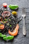 Spaghetti made from black pasta and shrimp — Stock Photo