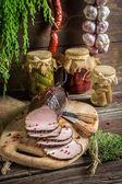 Freshly sliced smoked ham and marjoram — Stock Photo