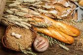 Olika typer av fullkornsbröd på gamla träbord — Stockfoto