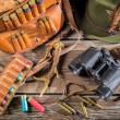 Bag with bullets, binoculars and hat in a hunting lodge — Stock Photo #48975875