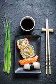 Fresh sushi, dark ceramic and chopstick — Stock Photo