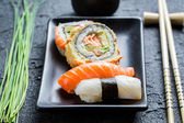 Closeup of fresh sushi, dark ceramic and chopstick — Stock Photo