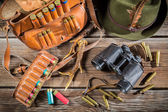 Bag with bullets, binoculars and hat in a hunting lodge — Stock Photo