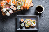 Sushi served with soy sauce on black stone — Stock Photo