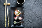 Sushi serviert auf eine schwarze Keramik mit Sojasauce — Stockfoto