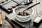 Thin pipe in glass ashtray with cigarettes and lighter — Stock Photo