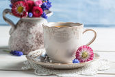 Spring flowers and coffee on old table — Stock Photo