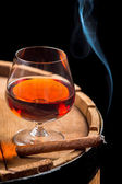 Smoking cigar and wooden brandy barrel — Stock Photo