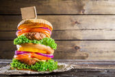 Double-decker burger on wooden background with space to menu — Stock Photo