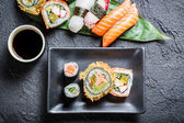 Sushi with soy sauce on black rock — Stock Photo