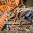 Bag with bullets, binoculars and hat in a hunting lodge — Stock Photo #49884877