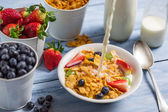 Pouring milk into cornflakes with fruits — Stock Photo
