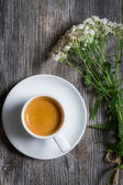 Espresso coffee and a small bouquet of flowers — Stock Photo