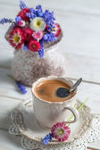 Cup of hot coffee and spring flowers — Stock Photo