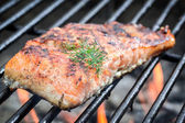 Baked salmon on the grill with fire — Stock Photo