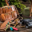 Bag with bullets, binoculars and hat in a hunting lodge — Stock Photo #51028029