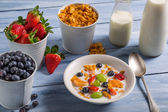 Preparations for breakfast corn flakes and fruits — Stock Photo