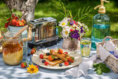 Summer breakfast in the garden with fruit toast with honey — Stock Photo