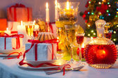 Candlelight and gifts all around the Christmas table — Stock Photo