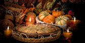Pumpkins and cake on candle light still life — Stock Photo
