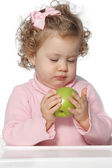 Baby girl eating fruit — Stock Photo