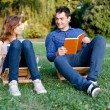 Young couple reading a book in the park — Stock Photo