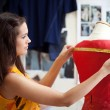 Foto Stock: Fashion designer measuring a dress. Shallow depth of field.
