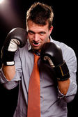 Businessman with boxing gloves guarding his face. High contrast. — Stock Photo