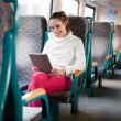 Cheerful young woman using tablet computer on the train — Stock fotografie