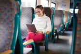 Cheerful young woman using tablet computer on the train — Stock Photo