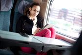 Mujer joven con tablet pc en el tren — Foto de Stock