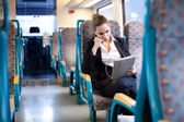 Businesswoman listening to music and using tablet computer on th — Stock Photo