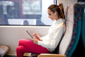 Young woman using tablet computer on the train — Stock Photo