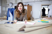 Happy fashion designer working on her designs in the studio — Stock Photo