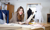 Fashion designer going through her sketches — Stok fotoğraf