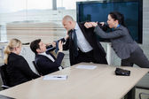 Businessman attacking his colleague at a meeting, grabbing him b — Stock Photo