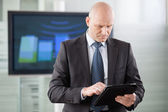 Businessman using tablet computer in conference room — Stock Photo