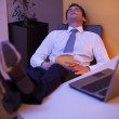 Businessman falling asleep while eating Chinese food in an office - Stock Photo