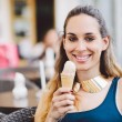 Young woman eating ice cream in outdoor cafe — Stock Photo