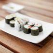 Plate of sushi rolls on a wooden table — Stock Photo
