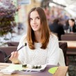 Young woman daydreaming while eating sushi — Stock Photo