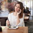 Beautiful young woman talking on the phone in a sushi restaurant — Stockfoto