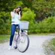 Young woman sitting on her bicycle and talking on the phone — Stock Photo