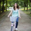 Young woman riding a bike in a park — Stock Photo