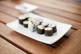Plato de sushi rollos en una mesa de madera — Foto de Stock