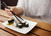 Detailed view of a woman eating sushi — Stock Photo
