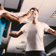 Stock Photo: Young man wiping sweat off of friend's face in gym