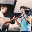 Young man motivating gym buddy during bicep exercise — Stock Photo